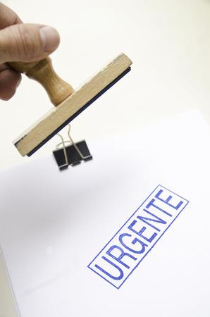 Spanish word urgente on white paper and human hand photo