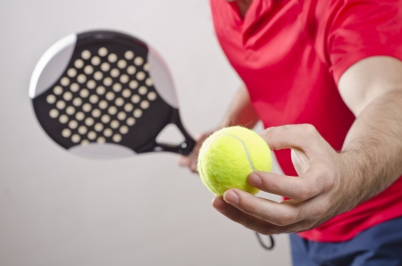 Paddle tennis player ready for serve on gray background photo