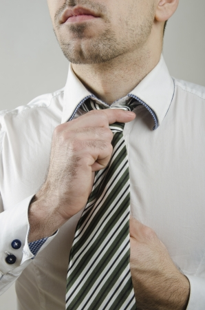 anonymous guy doing a tie knot in closeup frame