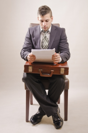 looking for a job: full Young businessman holding a curriculum or paper