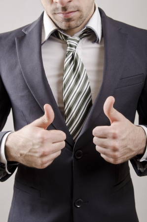 Suit young business man posing with focused thumbs up photo