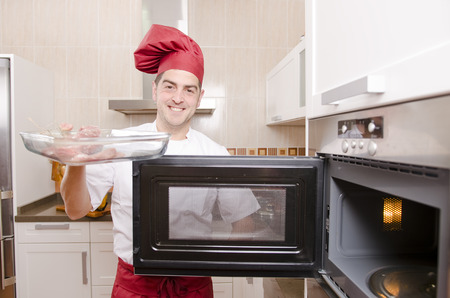 chef cooking with microwave oven in kitchen