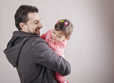 father and one year daughter isolated on gray  photo