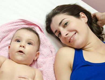 Lying mother and clean baby on towel photo