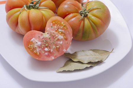 grocers: Raff tomato on dish with laurel leafs