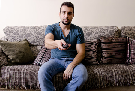 Man with remote control like couch potato