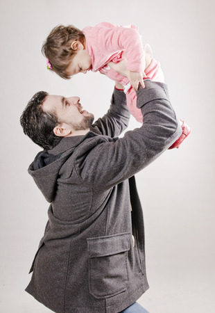 Isolated father lifting little girl up to the air photo