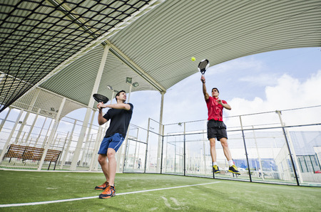Young paddle tennis  player with racket and ball in court Reklamní fotografie - 26937755