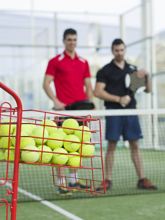 Paddle tennis training basket with pupils blured in background photo
