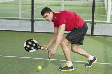 backhand: Amo tenis de la paleta listo para servir la bola con el rev�s Foto de archivo