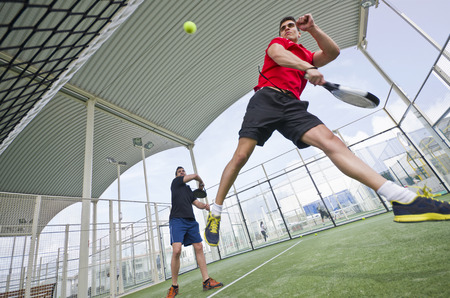backhand: Wide angle paddle tennis couple smashing ball in court