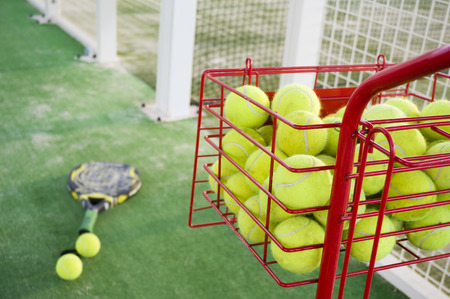 Paddle tennis objects, racket, balls, basket and court   photo