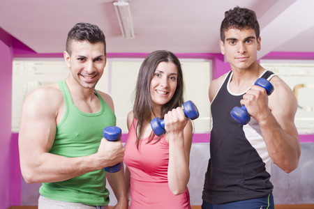 three young pose with blue dumbbells in gym room photo
