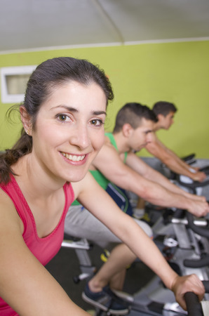 static bike: Spinning class in gym, girl looking at the view