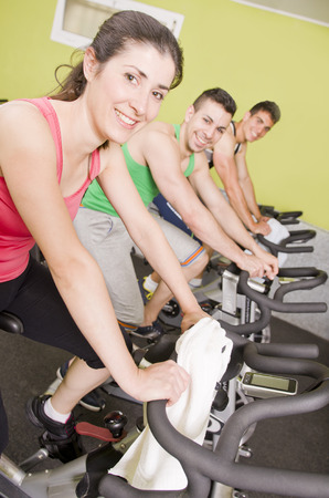 static bike: Smiling people on fitness spinning bike looking at the view Stock Photo