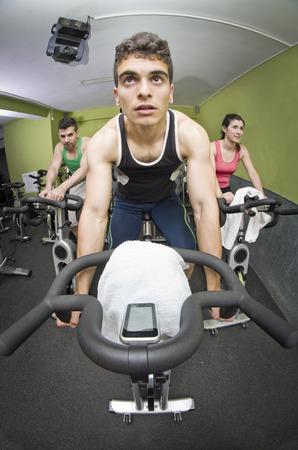 Fish eye image of young man on fitness bike photo