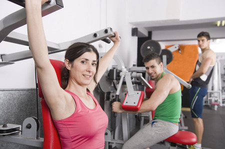 pectorals: Young fit People training with gym machines