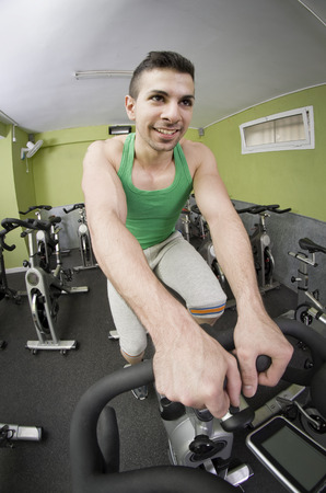 static bike: Fish eye spinning guy in gym smiling at run