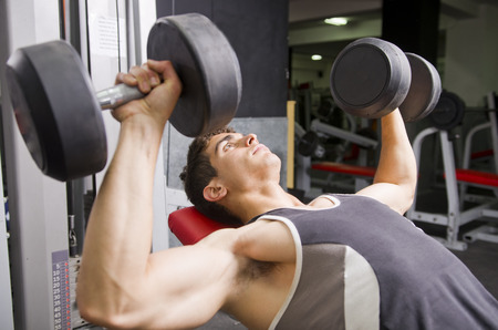 weight machine: Man and woman training at gym machines, shoulder and pecs exercises