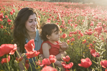 baby with his mother enjoying a field day outdoors, smiling in sunset backlight photo