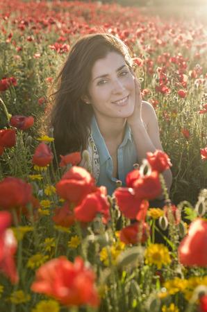 amongst: Beauty brunette girl posing in field amongst flowers