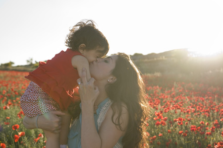 baby with his mother enjoying a field day outdoors, kissed in sunset backlight photo