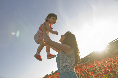 baby with his mother enjoying a field day outdoors, smiling in sunset backlight flare photo