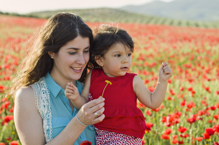 baby with his mother enjoying a field day outdoors photo
