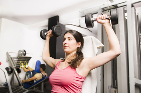 pectoral: Woman doing shoulder exercise with gym dumbbells