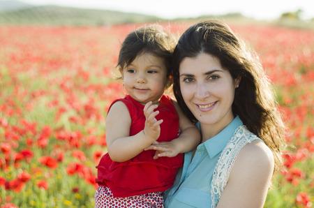 madre soltera: Madre y bebé posando en el campo de amapolas al aire libre Foto de archivo