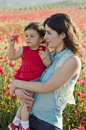 red haired: Moter and baby in poppies field smeling flowers