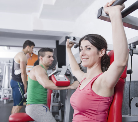 Woman doing shoulder exercise with gym machines photo