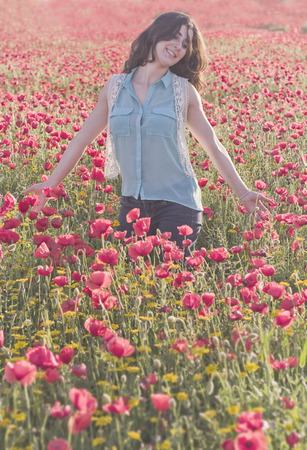 Brunette girl posing into the poppies flowers photo