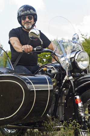 Senior man on custom sidecar motor bike smiling photo