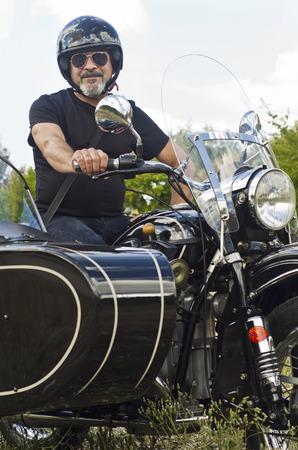 Senior man on custom sidecar motor bike smiling photo