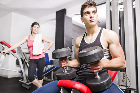 Man and woman at fitness room gym resting photo