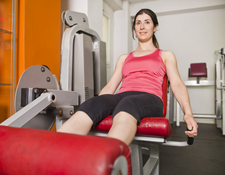 quadriceps: Woman doing quadriceps exercises on gym machine Stock Photo