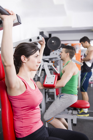 pectorals: Gym friends doing some shoulder exercises at gym Stock Photo