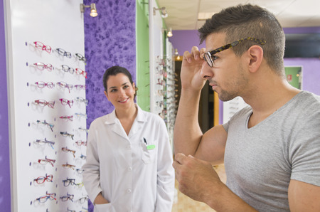 Young man choosing glasses in optical store with optometrist woman in background photo