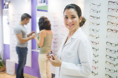 doctor of optometry: Optometis looking at the view in glasses store and couple in the background choosing lenses