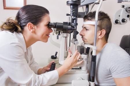 oculista: Optometrista silla y lámpara de hendidura, oftalmología dioptrías de calibración en el laboratorio oculista de mujer joven médico con lámpara latina joven. Foto de archivo