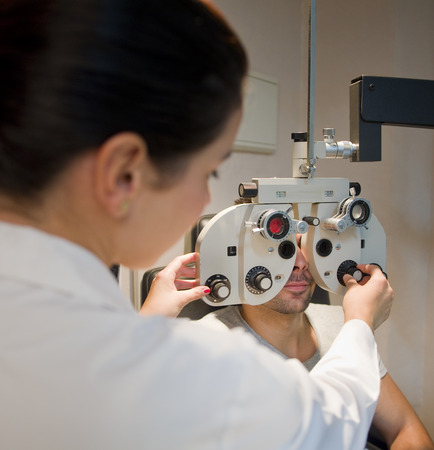 diopter: Optometrist chair and slit lamp, ophthalmology diopters calibration in oculist lab of young woman doctor with young latin lamp. Ambient light. Stock Photo