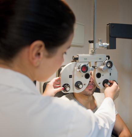 oculista: Optometrista silla y l�mpara de hendidura, oftalmolog�a dioptr�as de calibraci�n en el laboratorio oculista de mujer joven m�dico con l�mpara latina joven. La luz ambiental. Foto de archivo