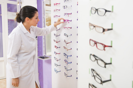 Optometrist looking at the products in glasses store photo
