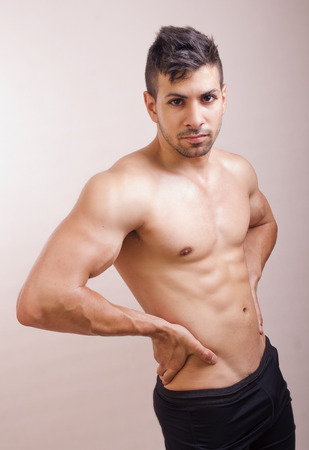 metrosexual: Young an with fit torso and muscles posing in studio shot Stock Photo