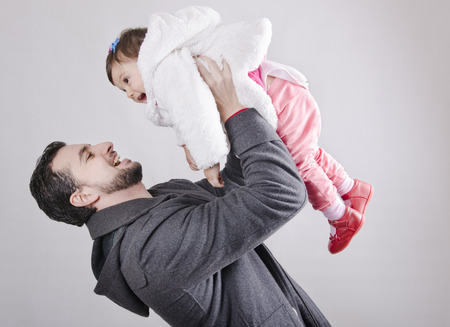 Father lifting his baby daughter up in the air with winter clothes in studio shot photo