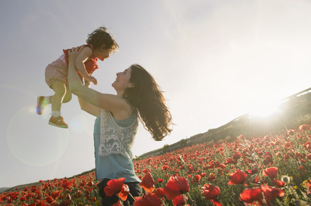 baby with his mother enjoying at poppies field day outdoors Standard-Bild