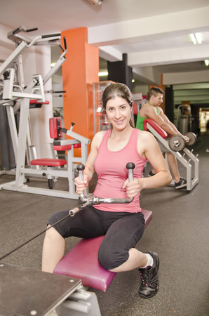 pectoral: Woman posing in gym at rowing fitness machines and guy in the background Stock Photo
