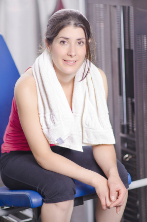 quadriceps: Woman in gym quadriceps machine resting with towel. Smiling and looking at teh view.