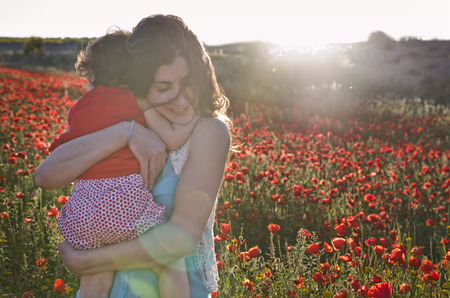 latin mother: Mother hugs lovely child daughter in poppies field with sunset sunlight and flare effect Stock Photo